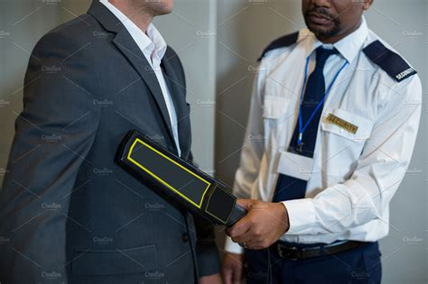 Airport security officer using a hand held metal detector